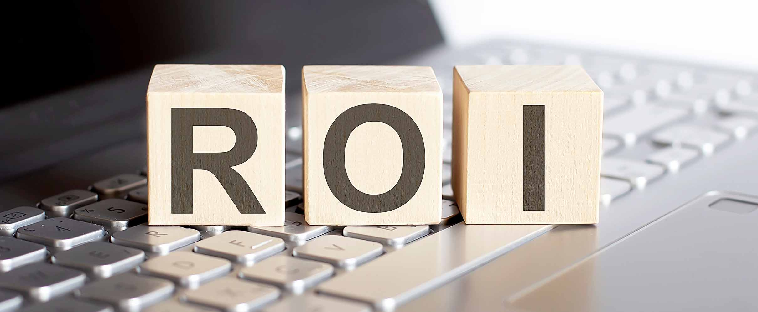 Three large wooden cubes spelling out 'ROI'.