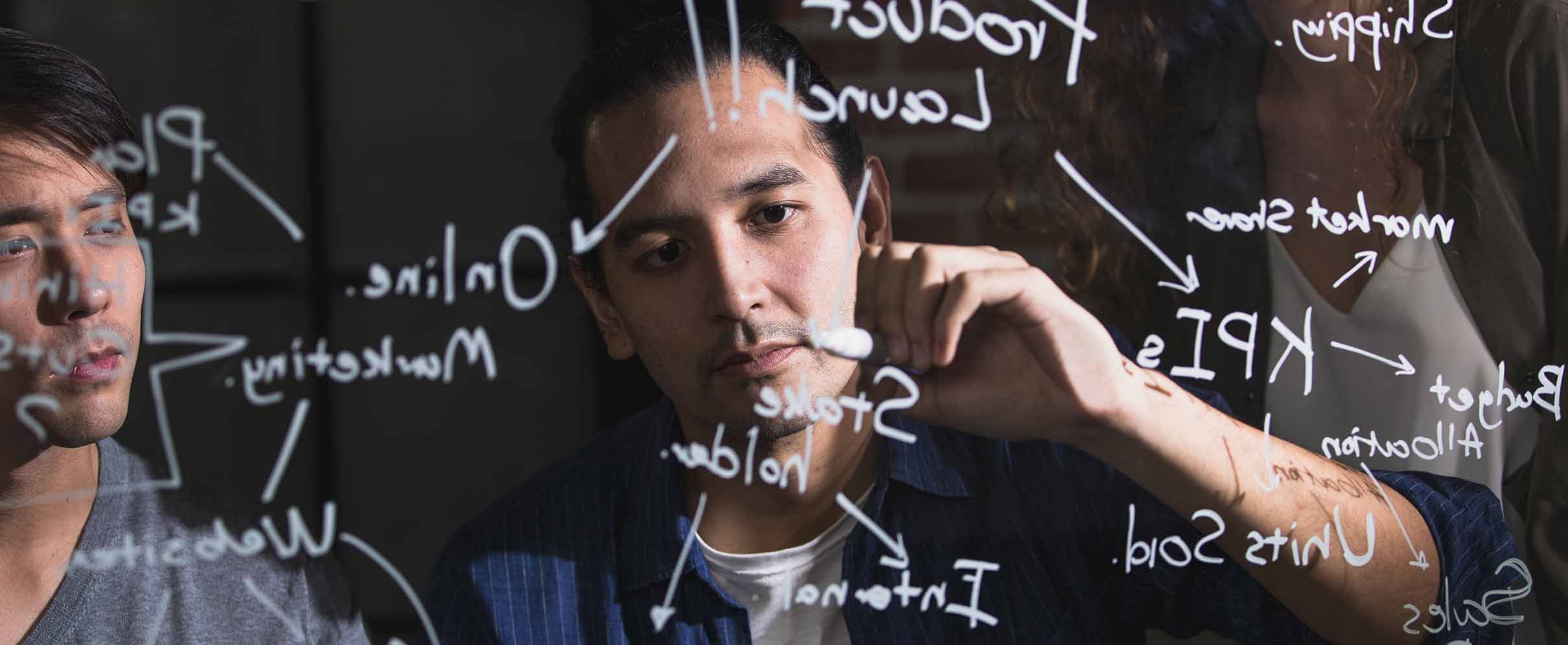 A man maps his affiliate marketing strategy on a clear wall.